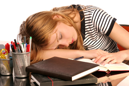 Young woman, tired of studying, sleeping over books
